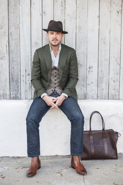 With white shirt, vest, olive green jacket, jeans, hat and big bag