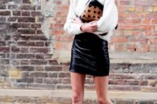 With white sweater, black leather mini skirt and printed clutch