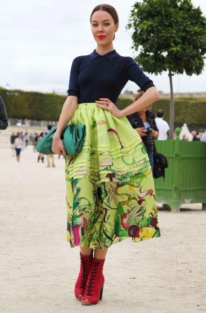 a navy shirt, red booties, an emerald clutch and a printed greenery skirt