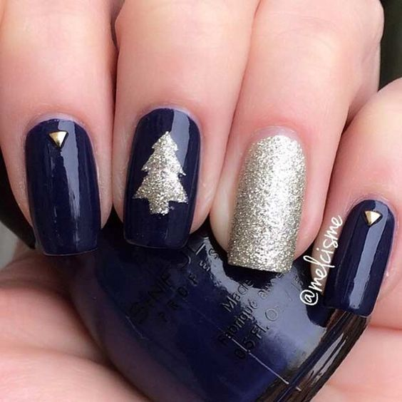 navy nails with a glitter tree, accent nail and gems