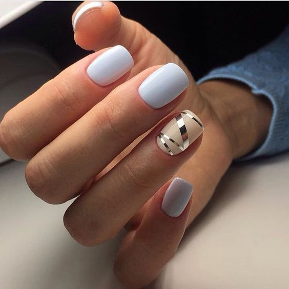 white manicure with a beige and silver stencil nail