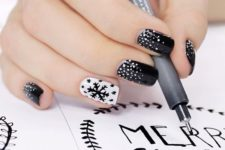 14 black nails with white snow, a white accent nail with a black snowflake