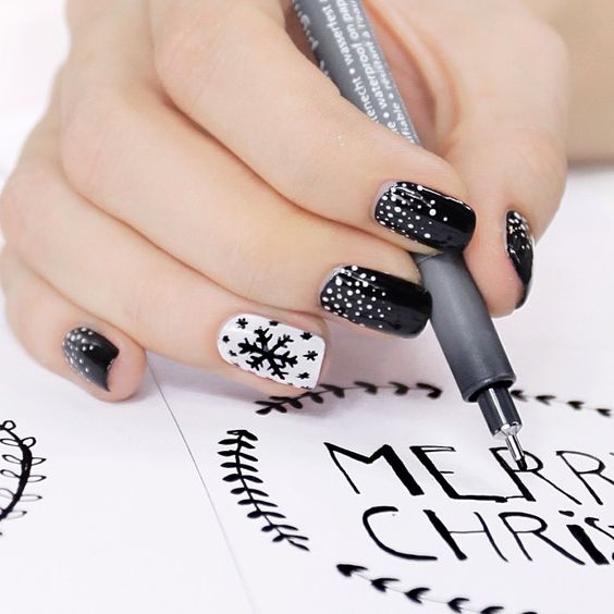 black nails with white snow, a white accent nail with a black snowflake
