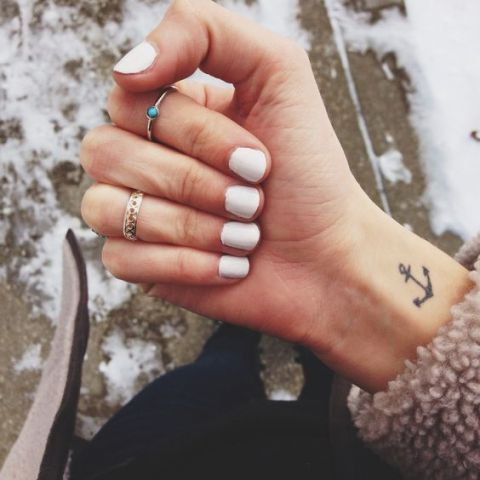 Black anchor tattoo on the right wrist