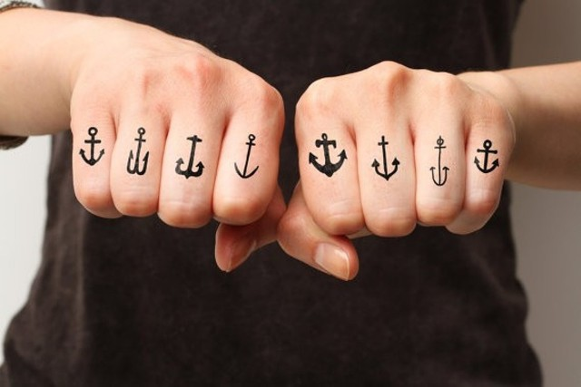 Black anchor tattoos on the fingers