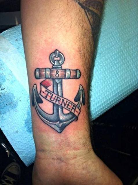 Blue, red and brown anchor tattoo on the left wrist
