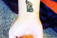 Gray elephant with heart balloon tattoo