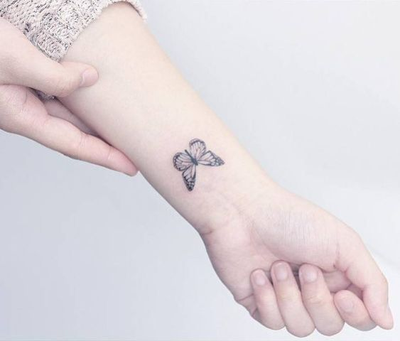 Simple black butterfly tattoo on the left wrist