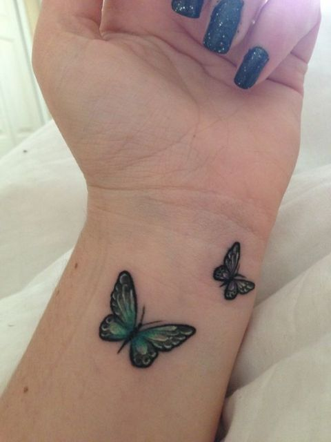 Two green butterflies on the left wrist