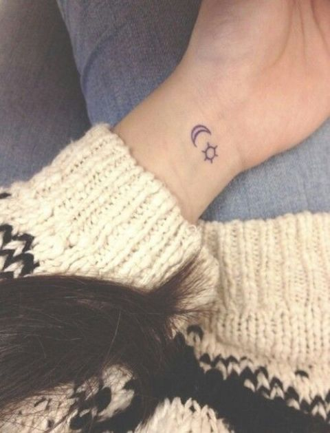 Two small tattoos on the left wrist