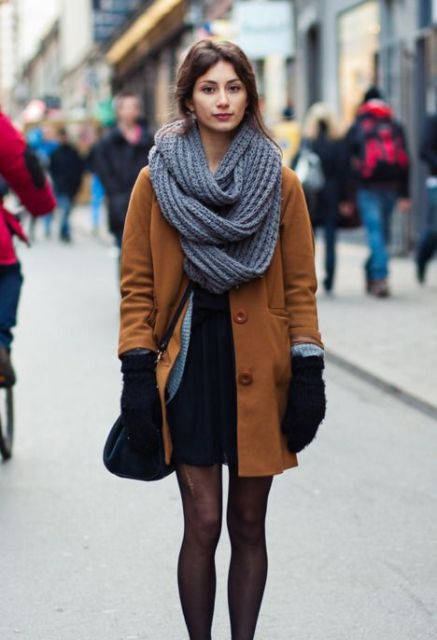 Office-worthy winter outfit with black dress, black tights, brown coat and mittens