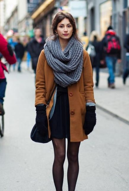 With black dress, brown coat and crossbody bag