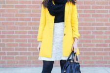 With black shirt, light gray skirt, black tights, ankle boots, leather bag and yellow mini coat