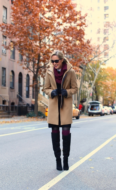 With camel coat, black dress and high boots