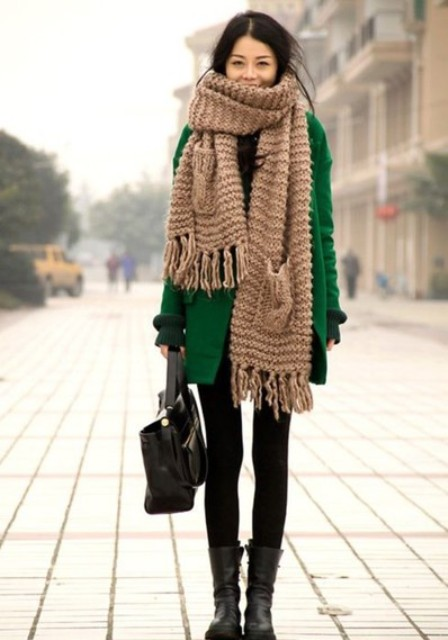 With green coat, dress, mid calf boots and leather bag