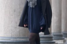 With navy blue mini dress, gray boots and black coat