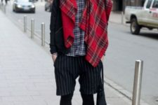 With plaid shirt, striped shorts, leather boots and cap
