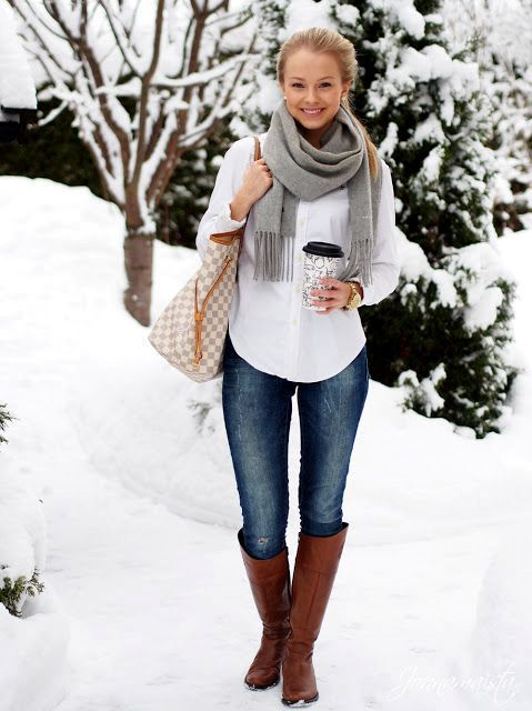 With white shirt, jeans, high brown boots and printed bag