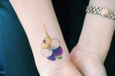 Yellow, white, purple and green flower tattoo