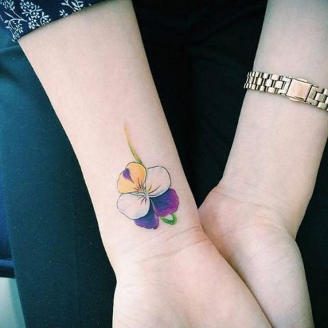 Yellow, white, purple and green flower tattoo