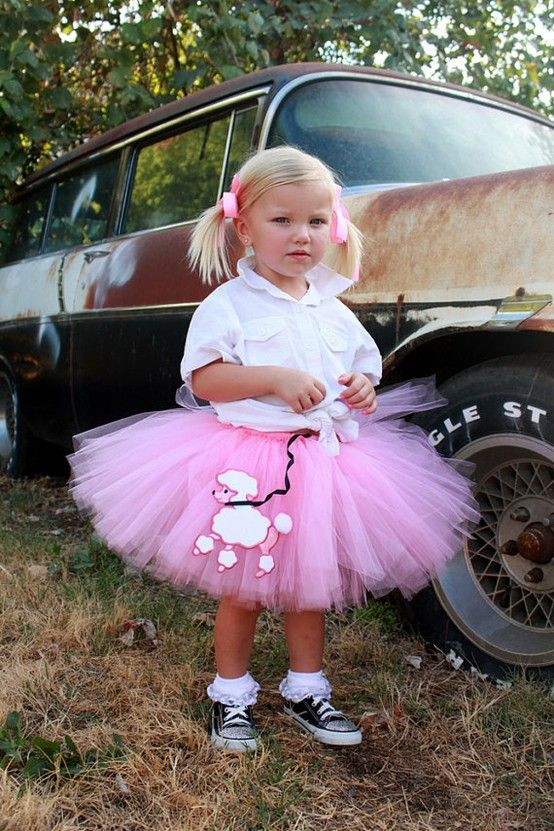 a pink tutu, a white shirt and black Converse