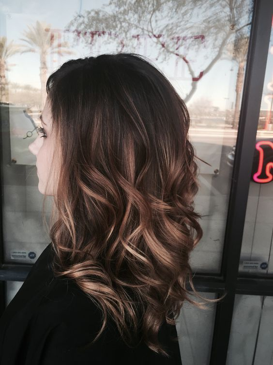 medium wavy dark hair with caramel and bronde highlights