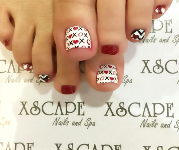 black and white nail design with red touches and XO