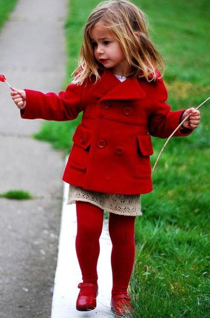a red coat, red shoes and tights, a lace dress