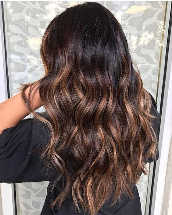 wavy black hair with caramel highlights looks natural