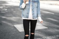 11 a white sweater, ripped black jeans, a blue denim jacket and ankle boots