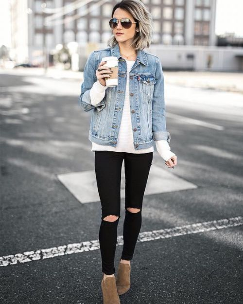 a white sweater, ripped black jeans, a blue denim jacket and ankle boots