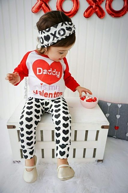 a black, white and red look with heart-printed pants, a printed sweatshirt, flats
