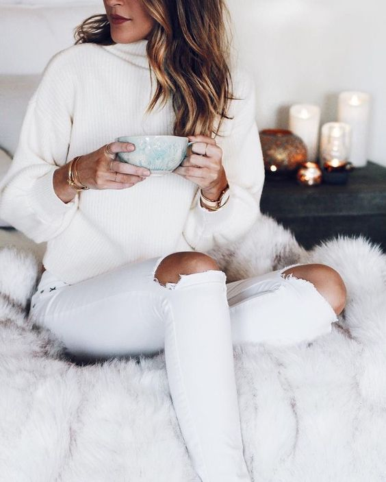 ripped white jeans and a white chunky knit sweater