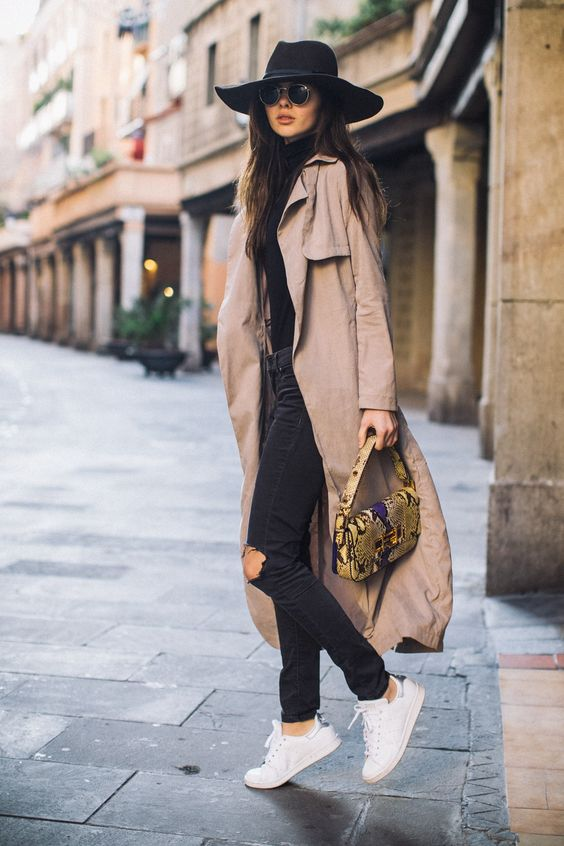 a black tee, black ripped jeans, white sneakers and a camel coat