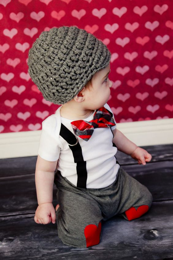 grey pants with hearts, a white tee, suspenders, a striped bow tie and a beanie