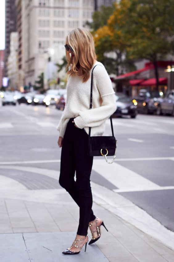 black heels, a white chunky knit sweater and black denim
