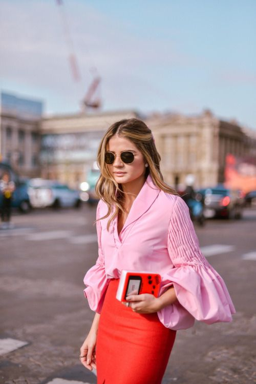 a pink shirt with unusual sleeves and a red skirt