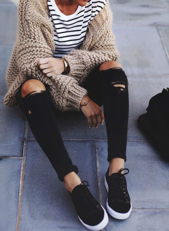 black ripped jeans, black sneakers, a striped t-shirt and a chunky knit brown cardigan