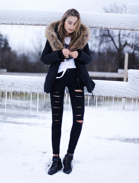 ripped black denim, flat boots, a printed tee and a parka
