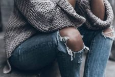 22 ripped jeans, a chunky knit oversized sweater and white sneakers