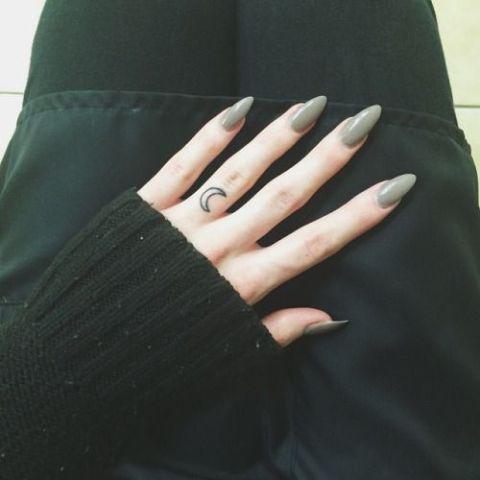 Black contour moon tattoo on the finger