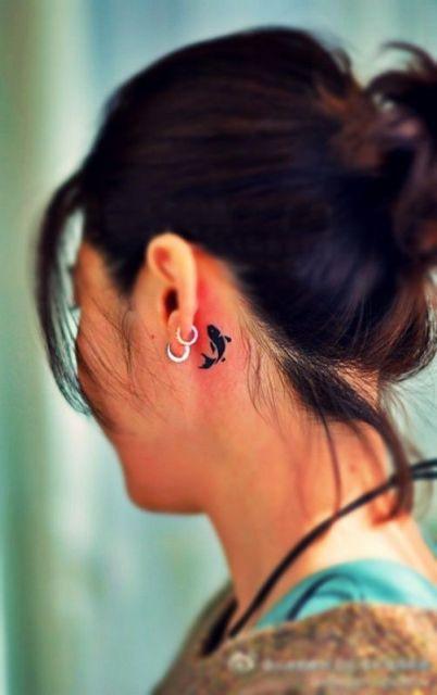 Black tattoo behind the ear
