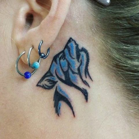 Blue wolf tattoo behind the ear