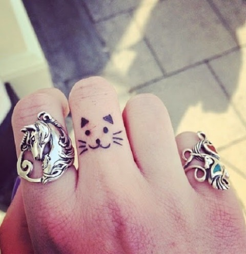 Small cat tattoo on the finger
