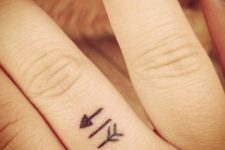 Tiny arrow tattoo on the finger
