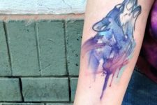 Wolf and moon tattoo on the arm