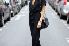 02 a black jumpsuit with a plunging neckline and black Vans