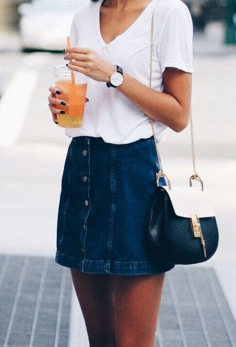 a buttoned denim mini skirt, a V cut white t shirt and a crossbody bag