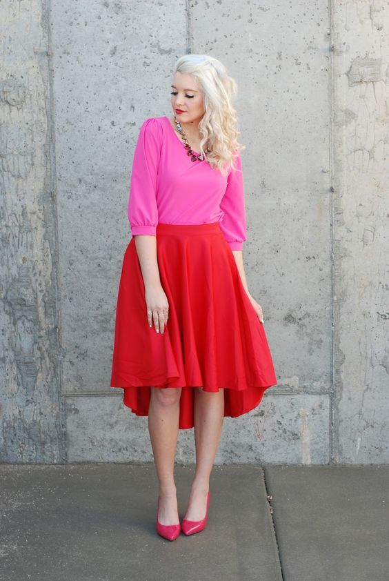 a pink top, a high low red skirt, pink heels
