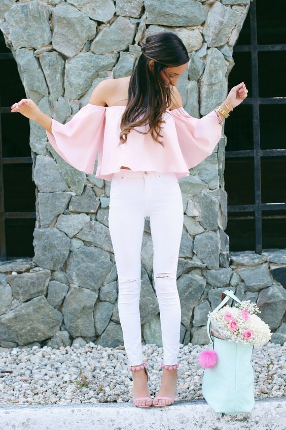 a pink off the shoulder crop top with white ripped jeans and a mint leather bag
